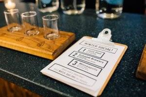 A clipboard with a piece of paper listing 3 options and a flight of three glasses. Rewire PBS Our Future Tap Water