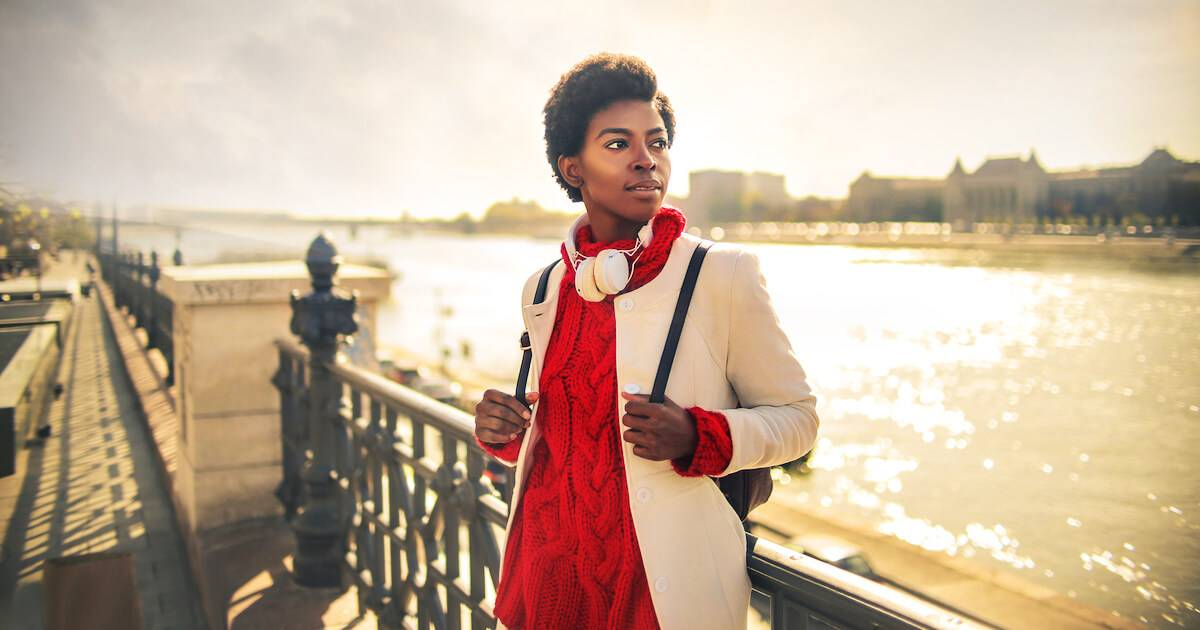 Photo of African-American woman looking over a river at her new city. Big Move pbs rewire