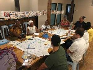 A group of people sit gathered around a table with lots of maps. Rewire PBS Our Future Tap Water