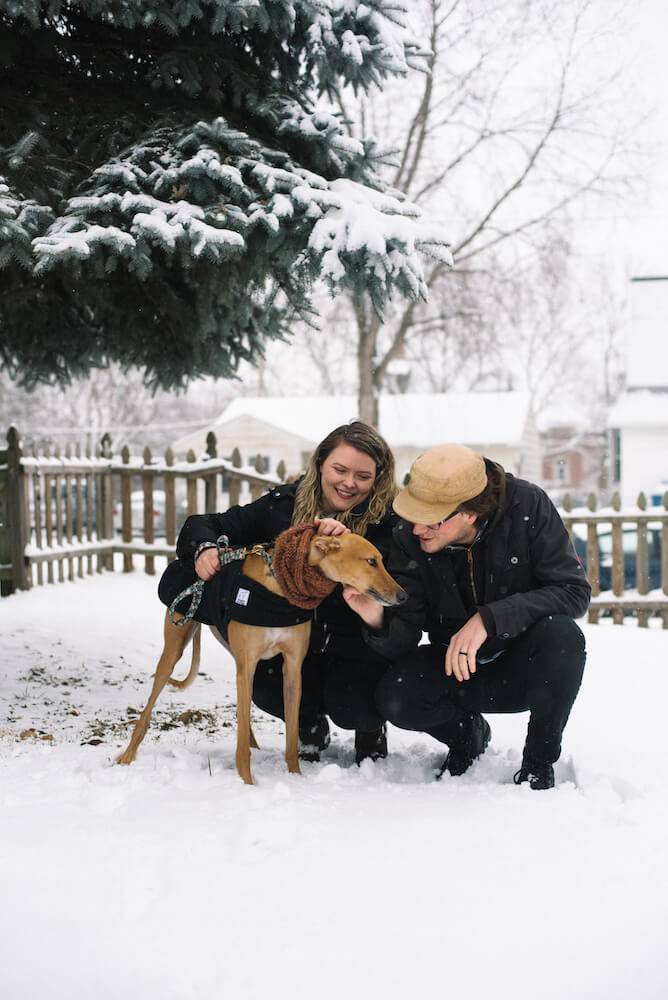 Photo of a couple and their fawn-colored greyound, all posing in the snow. Rewire PBS Living Greyhound
