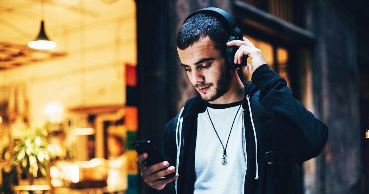 Hispanic man with headphones looking at his smartphone. Finsta pbs rewire