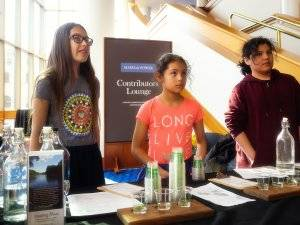 """Three young women, identified as """"youth water tenders"""" serve water from behind a table. Rewire PBS Our Future Tap Water"""