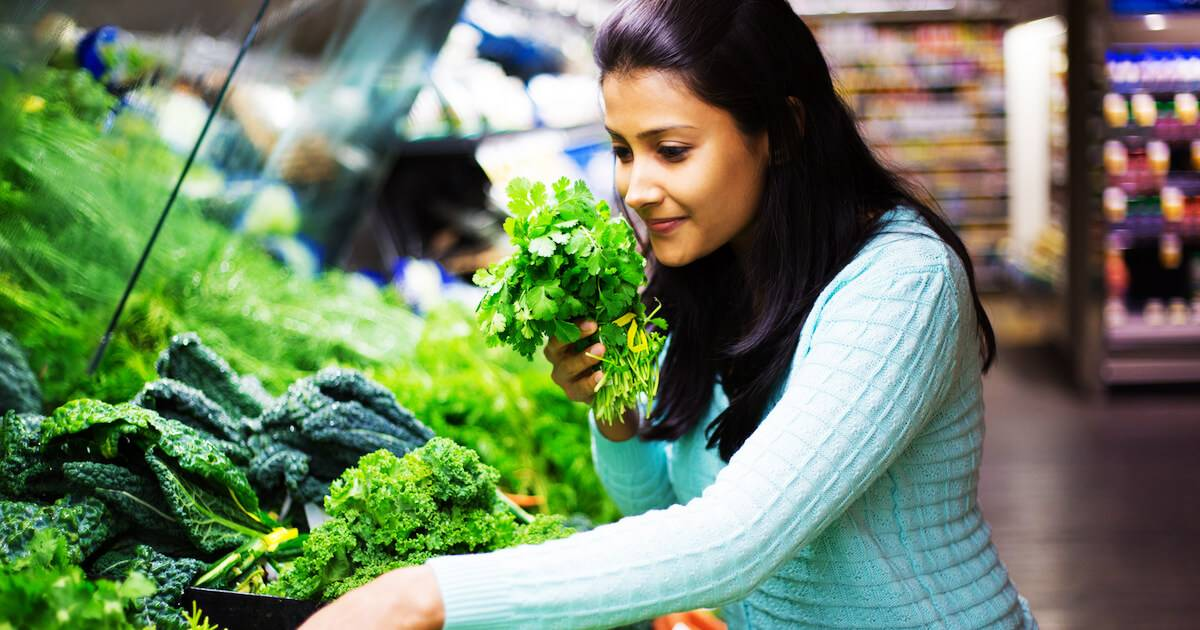Photo of young adult woman picking out leafy greens in a food co-op. Be More Green pbs rewire