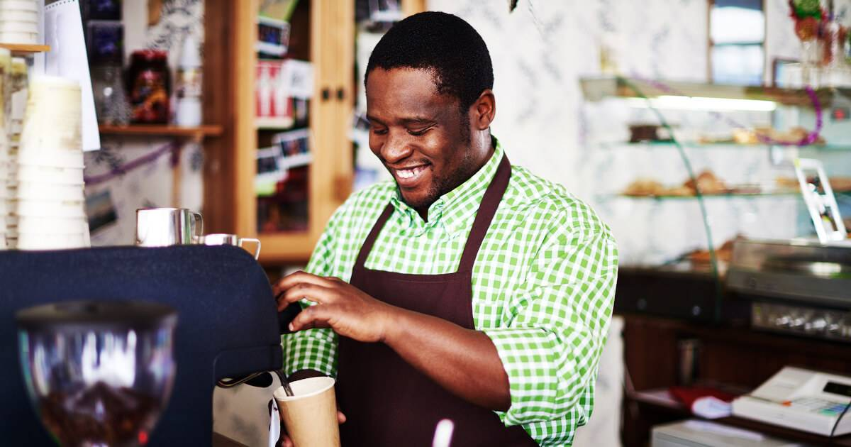 Photo of African-American man making a coffee drink at a cafe. Wage Theft pbs rewire