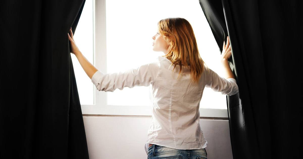 Photo of woman closing the blackout blinds on her windows. Energy Efficient pbs rewire