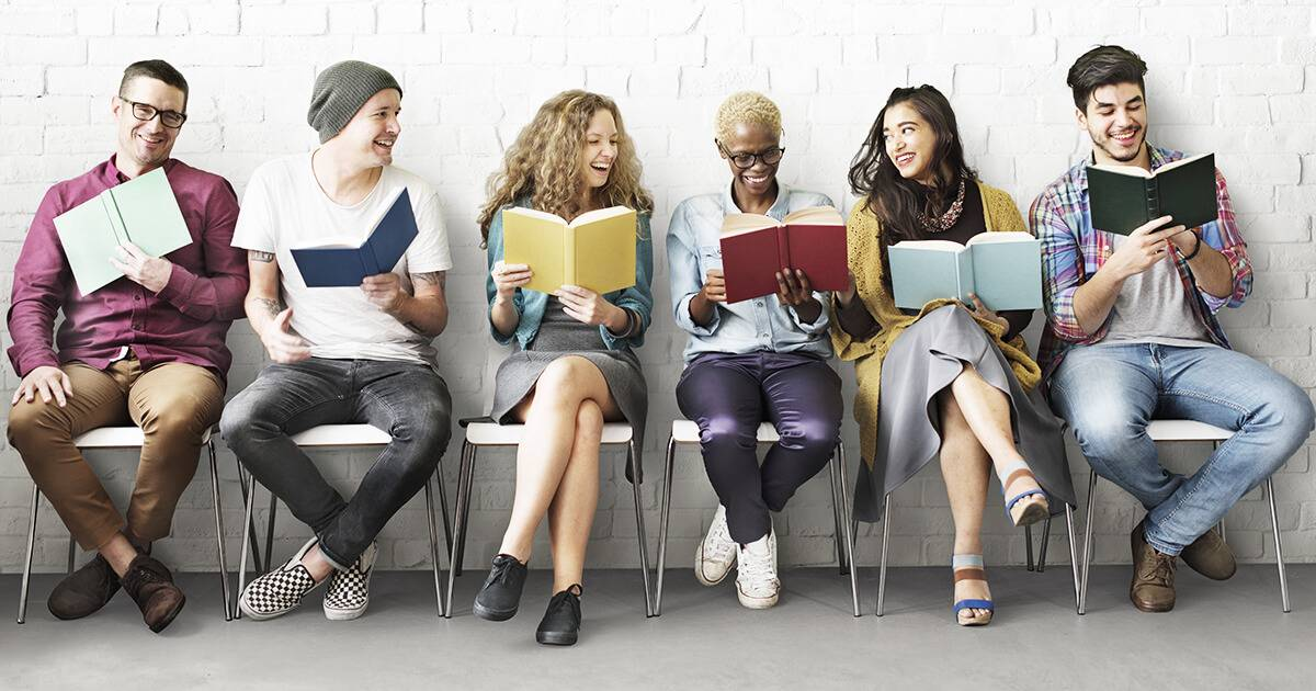 Photo of a group of people sitting in chairs along a wall, all reading and smiling. Rewire Living Reading Benefits PBS