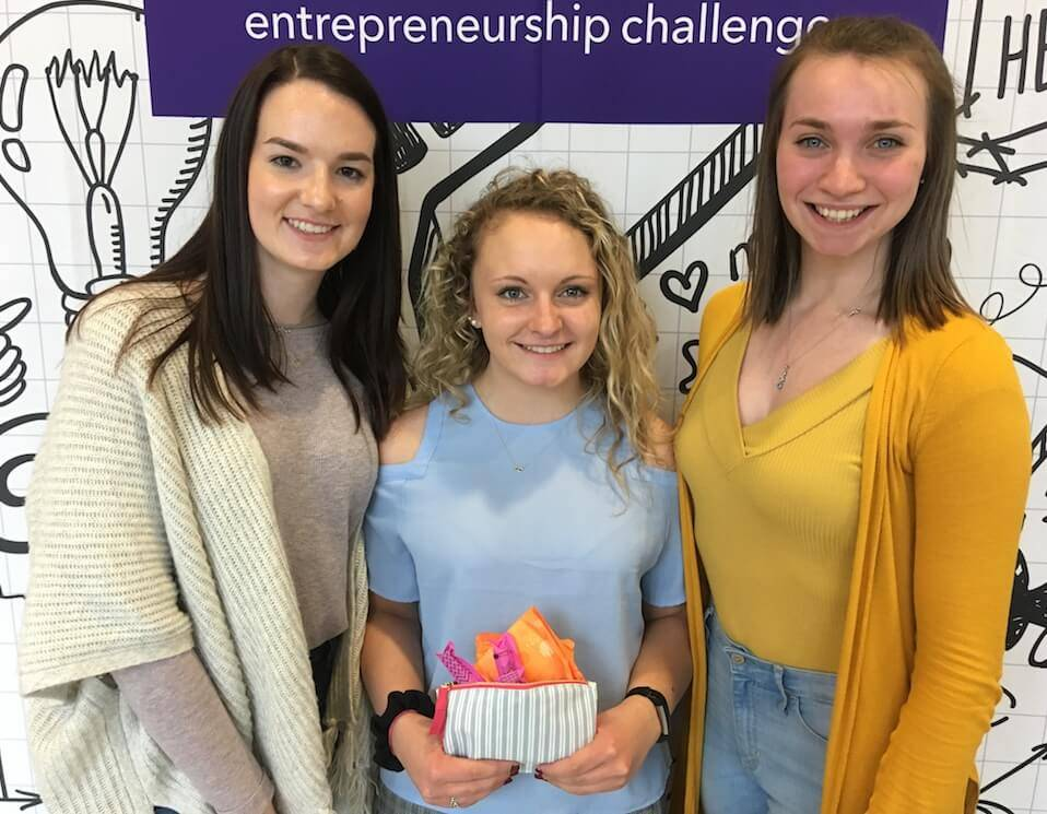 "Three young women pose in front of an ""entrepreneurship challenge"" banner at the e-Fest Entrepreneurship Challenge. Rewire PBS Work Student Entrepreneurs"