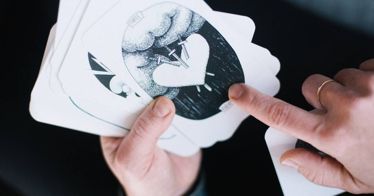 Photo of person holding and pointing at a tarot card. pbs rewire
