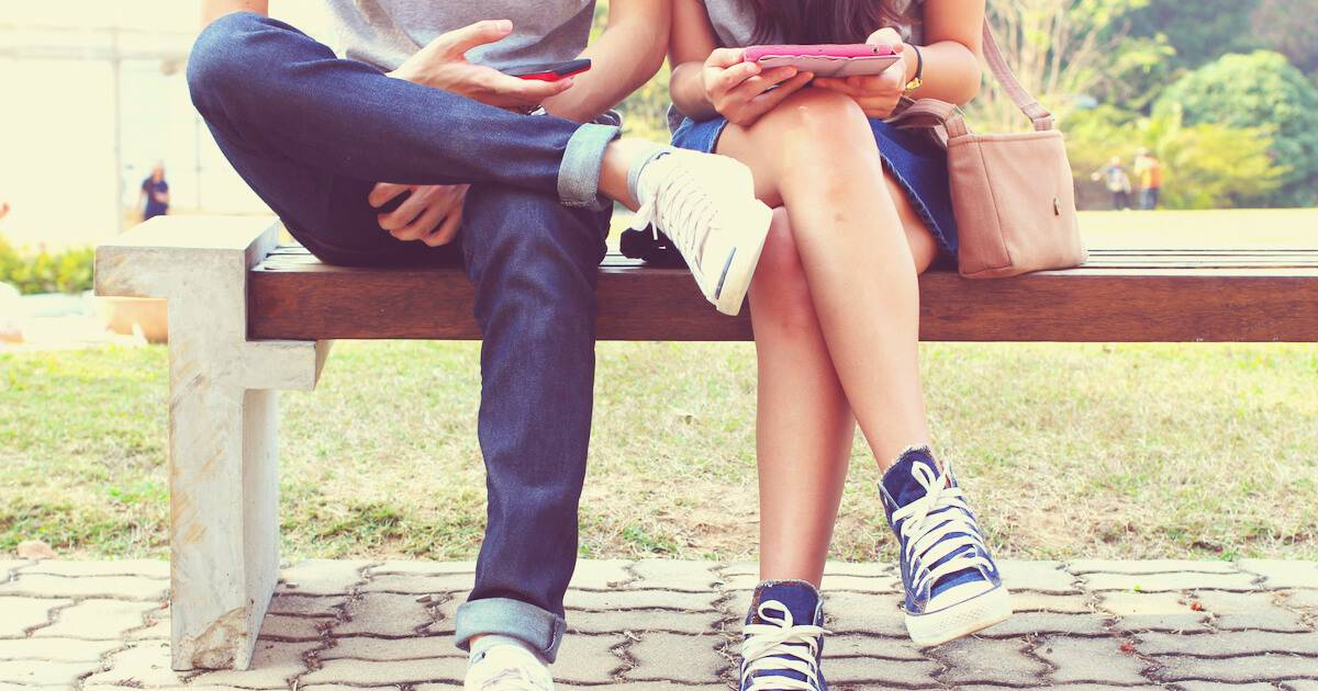 Photo of young couple sitting on bench while on their smartphones. Partner Won't Post pbs rewire
