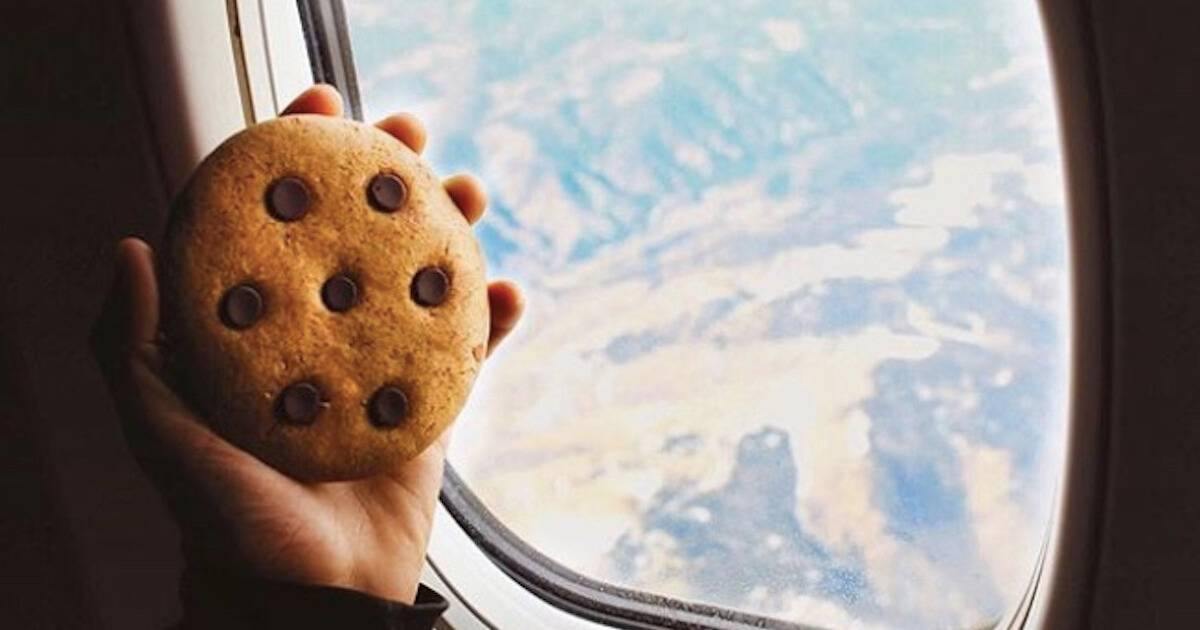 A hand holds a large cookie in front of an airplane window that's flying at altitude. Rewire PBS Work Student Entrepreneurs