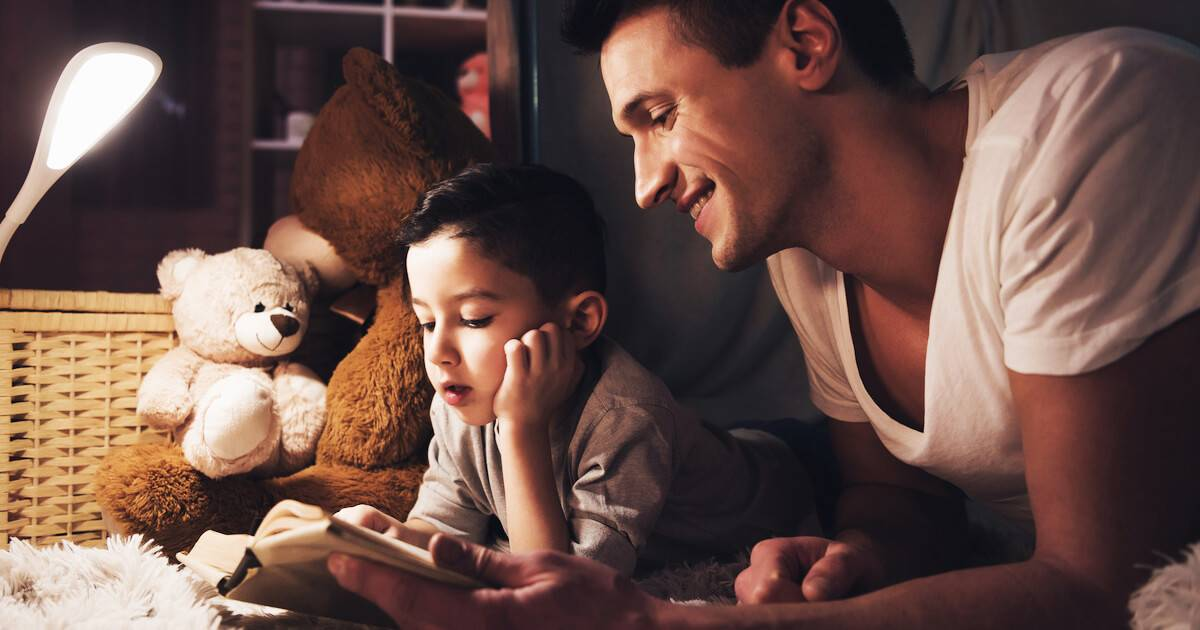 Photo of young father reading to son in a fort. Dad Guilt pbs rewire