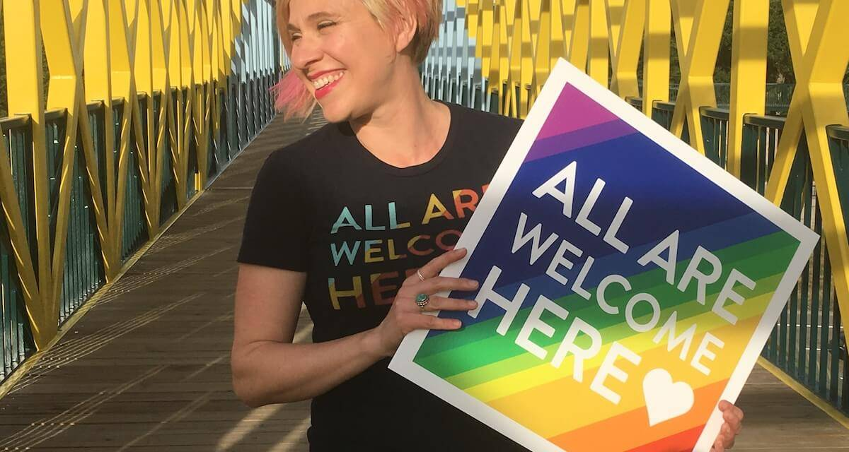 Photo of Jaime Chismar hold her All Are Welcome Here sign. Passion Project pbs rewire