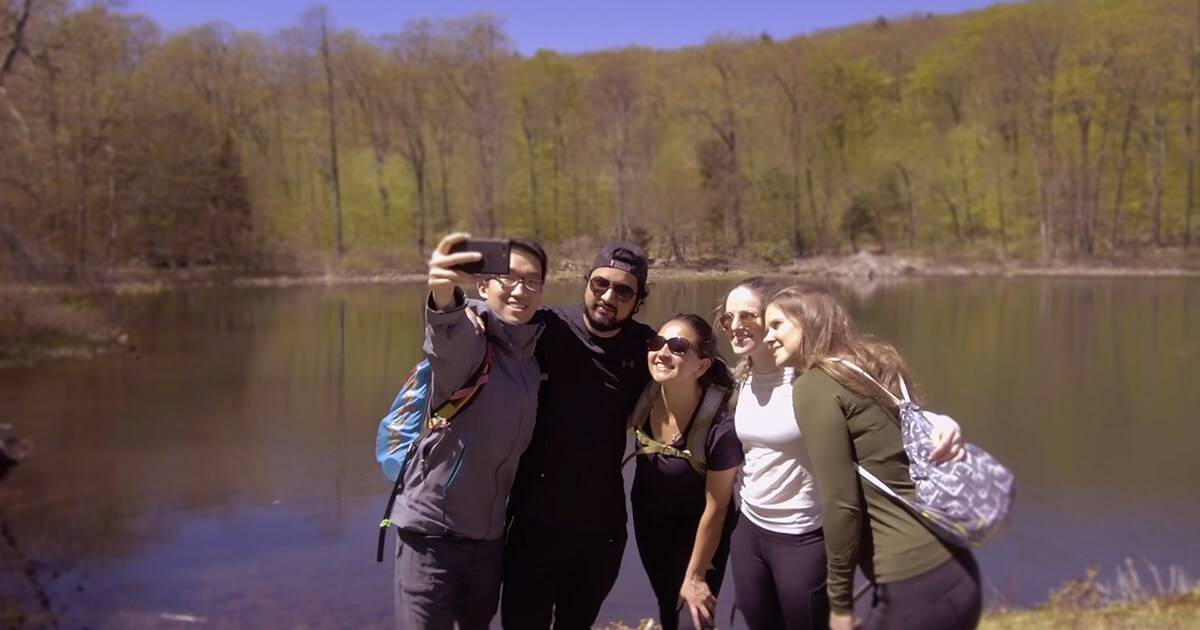 Photo of group of young people on adventure near a lake. Ridj-it pbs rewire