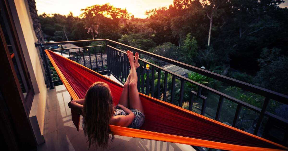 Photo of woman sitting in hammock on her apartment balcony. PTO pbs rewire