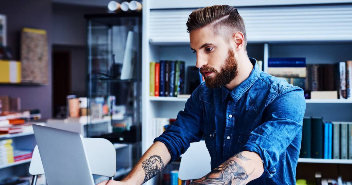 Photo of man with arm tattoos working at his office desk. Work Wardrobe pbs rewire