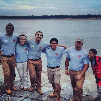 Photo of smiling volunteers lined up by a large body of water. Rewire PBS Work Humanitarian Gap Year