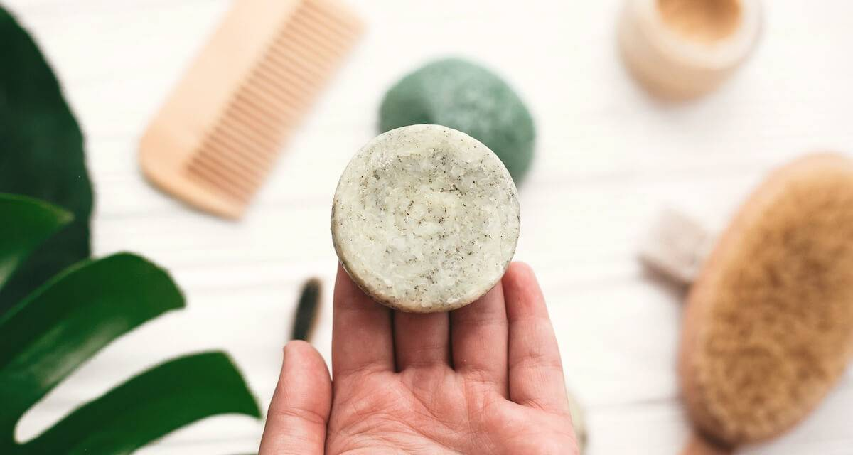 Hand holding natural solid shampoo bar on background of bamboo brush, deodorant, sponge on white wood with green monstera leaves. Rewire PBS Living Plastic