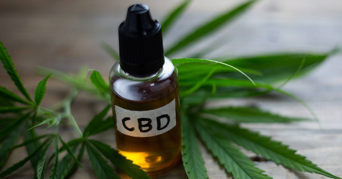 Small bottle of CBD oil surrounded by leaves on wood table.