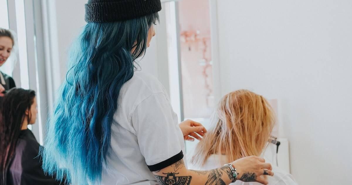 Photo of a hair stylist with blue hair cutting a female client's hair. Rewire PBS Work Trade School