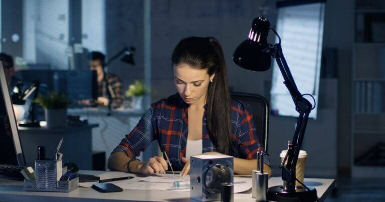 A woman works at a desk. Rewire PBS Work Internship