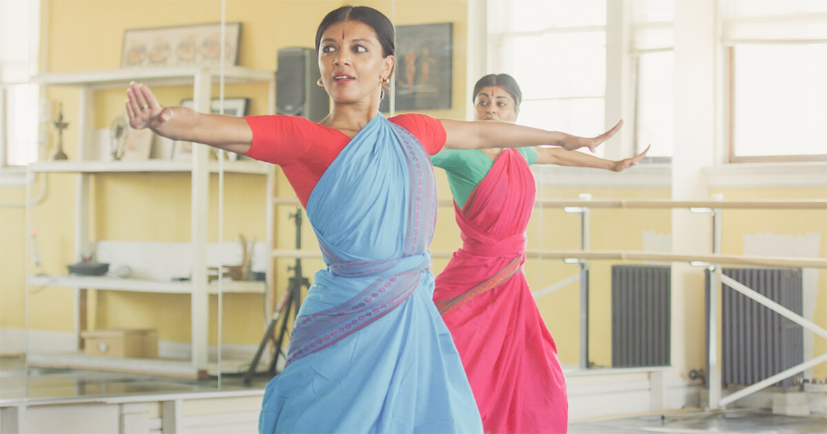 Two women dancing in colorful Indian traditional dresses. Rewire PBS Work Ragamala Dance Company