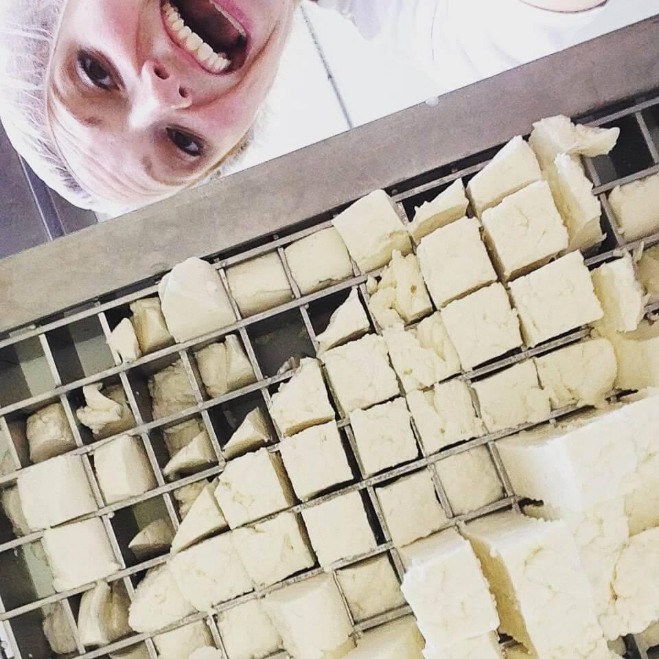 Selfie of woman smiling next to cheesemaking equipment. Rewire PBS Work Redhead Creamery