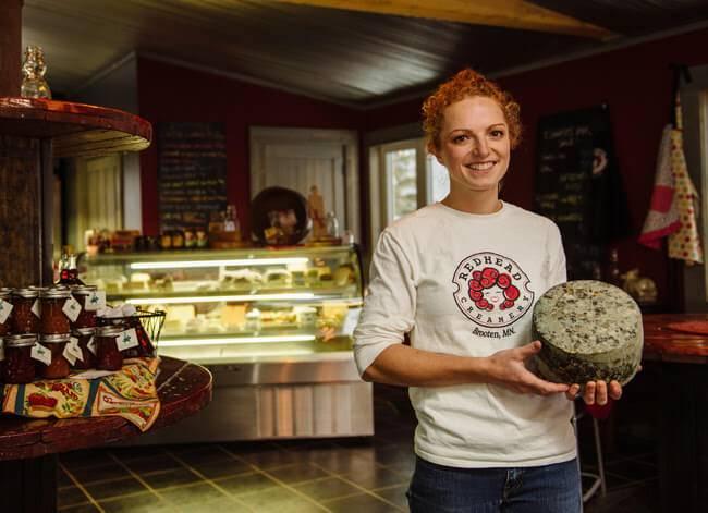 Photo of Alise Sjostrom in a Redhead Creamery sweatshirt, holding a wheel of cheese in her shop. Rewire PBS Work Redhead Creamery