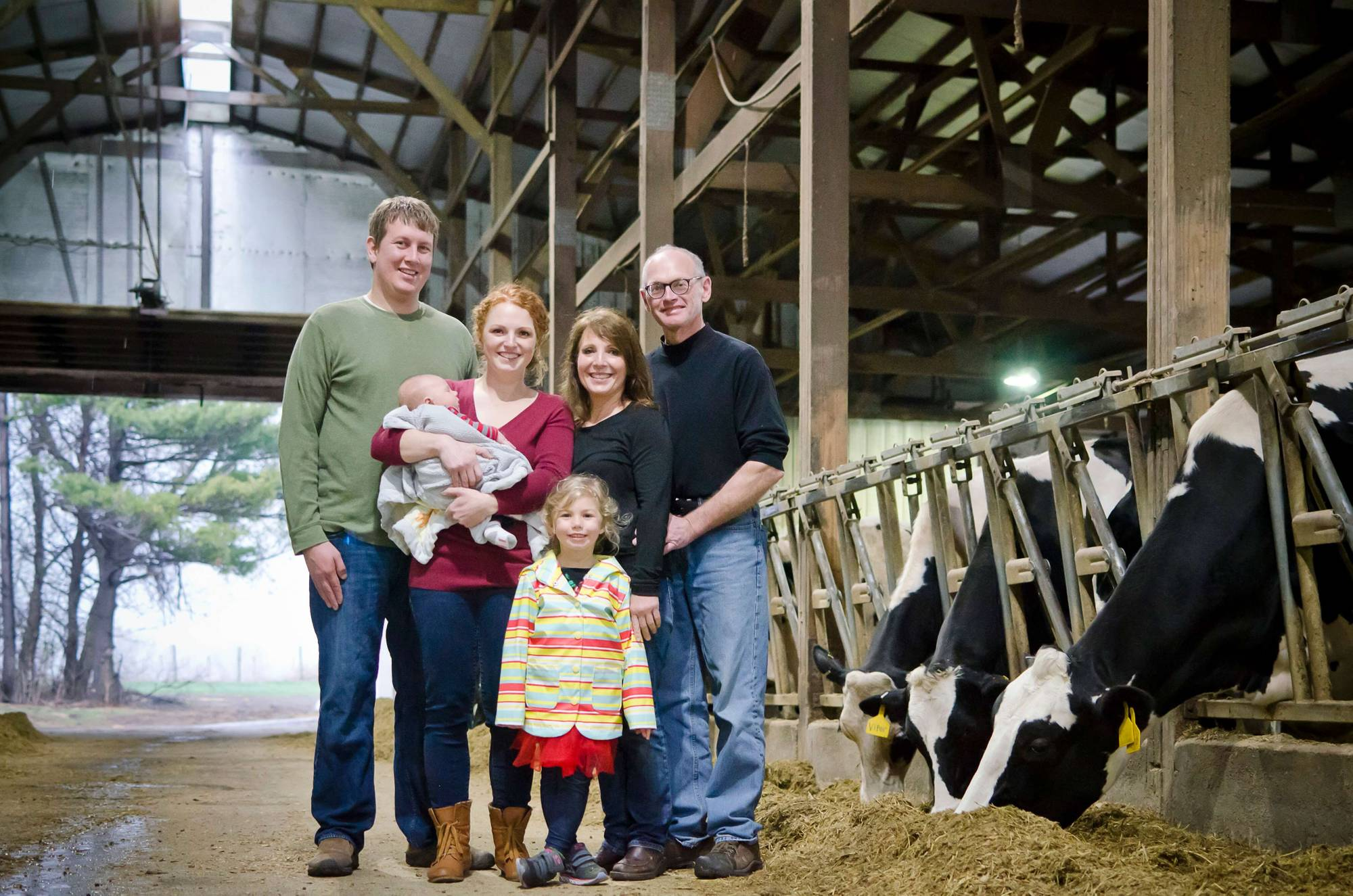 Three generations of a family, mom and dad, adult daughter and son-in-law, and two small children, pose in a dairy barn. Rewire PBS Work Redhead Creamery