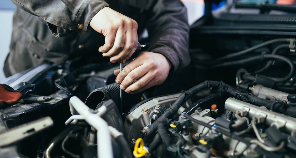 Photo cropped to show someone's hands working on a car's engine. Rewire PBS Living Mechanic