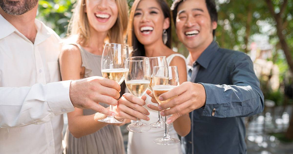 wedding guests toast champagne outdoors. PBS REWIRE Love wedding plus-one etiquette