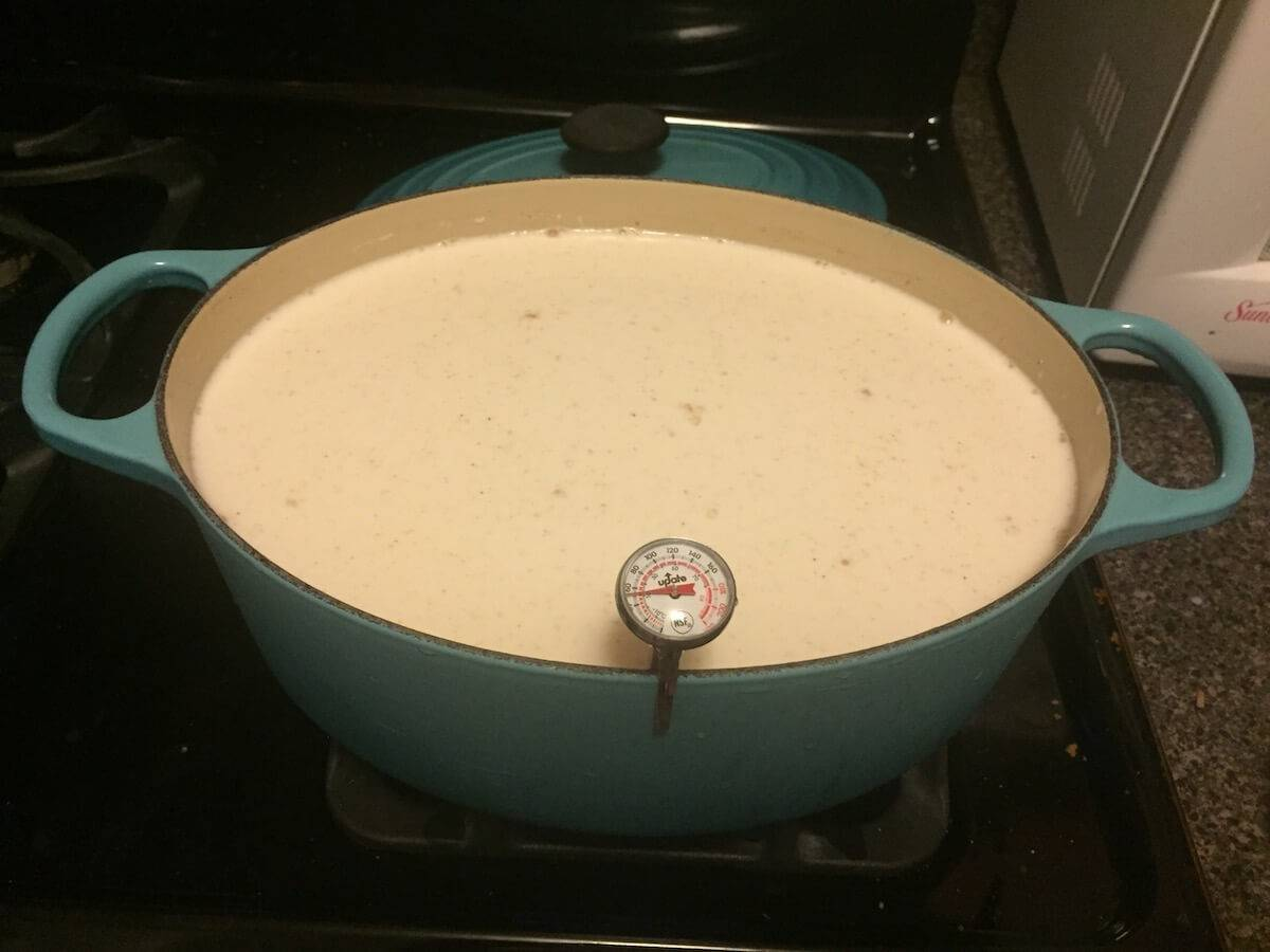 Photo of a large pot full of cream-colored liquid with a cooking thermometer. Rewire Living PBS Mozzarella