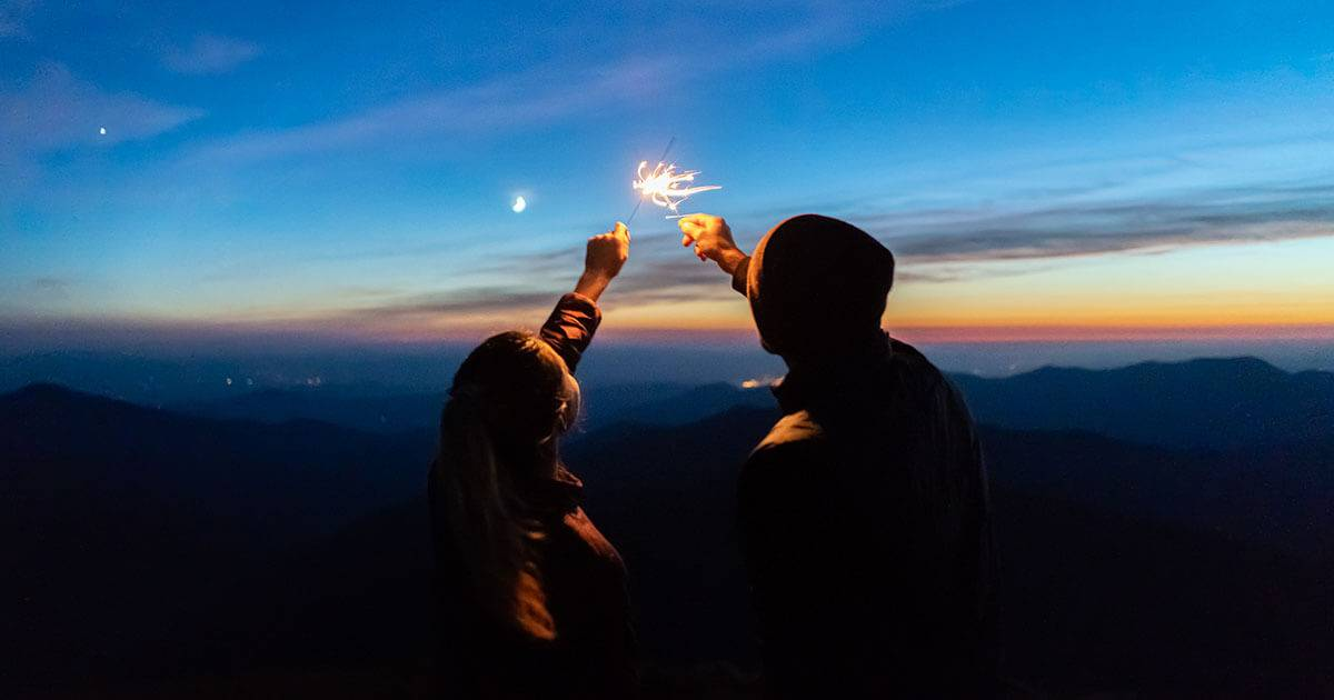 A couple hold sparklers against a dark sky. Rewire PBS Love Instant Connection