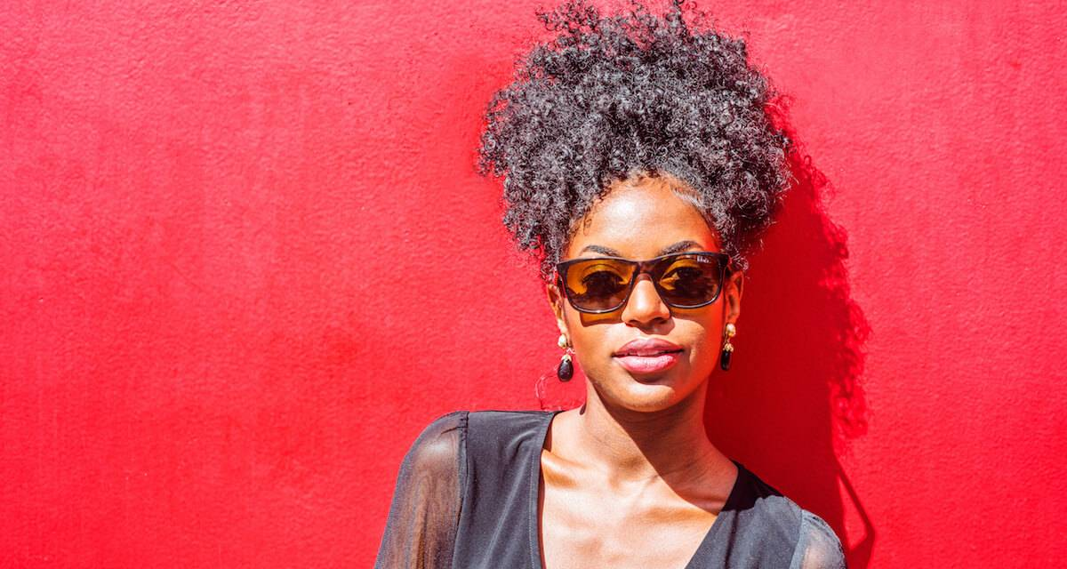 Black woman with natural hair and sunglasses standing against a red wall. Rewire PBS Work Natural Hair Bias