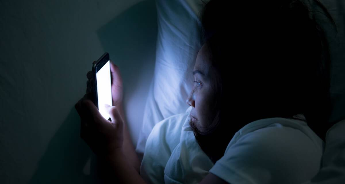 A woman looks at her phone in bed in the dark. Rewire PBS Love Friendships