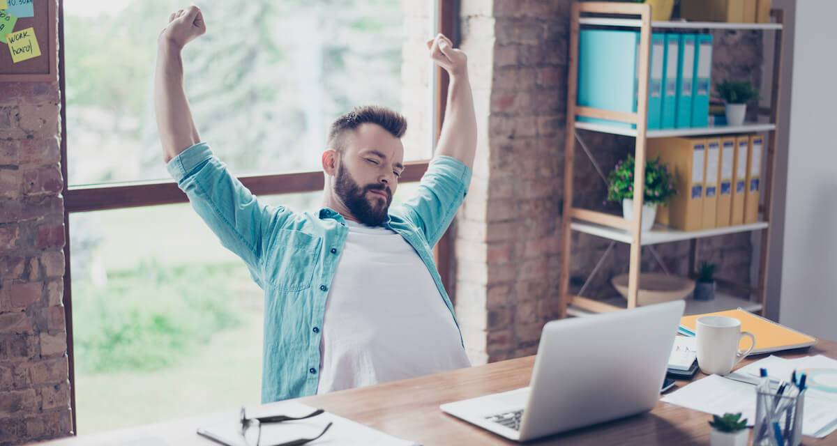 A bearded man stretching at his desk. Rewire PBS Work Self-care