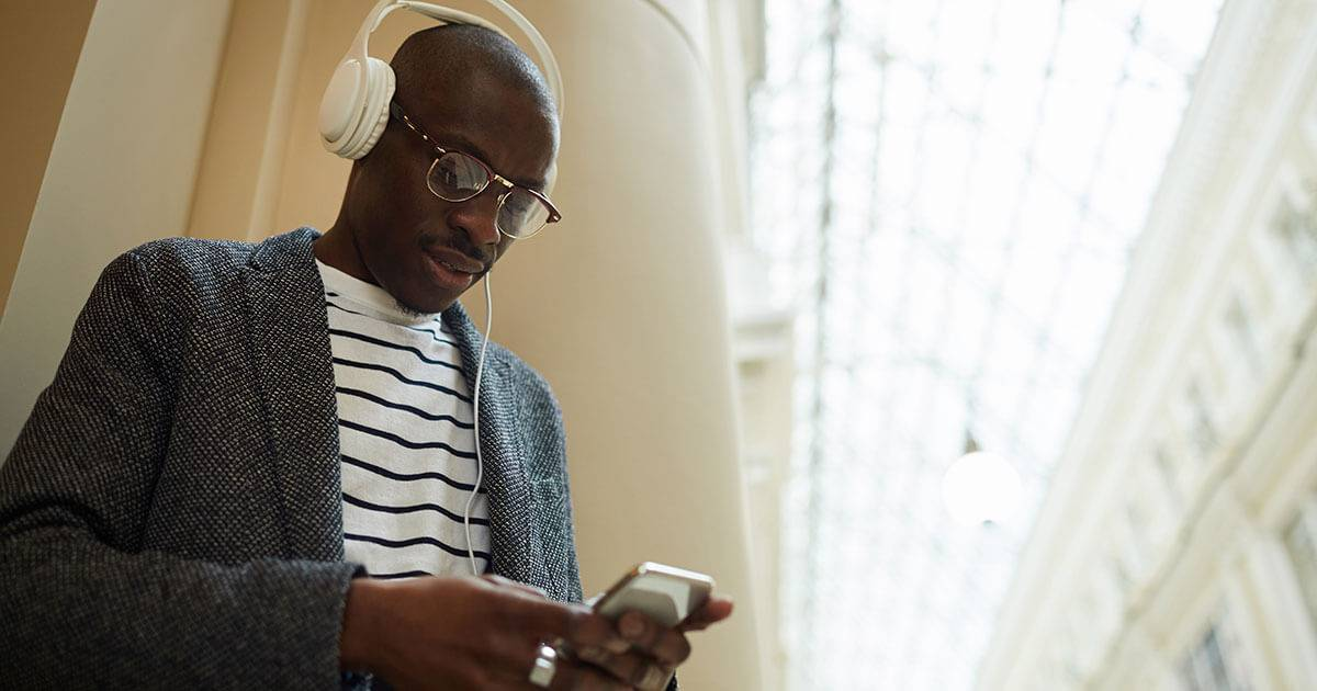 A man listening to headphones. Rewire PBS Living Audiobooks