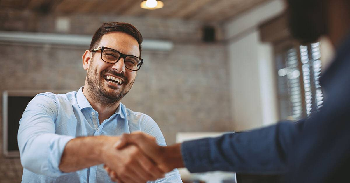 a young man shakes hands at an office job interview. REWIRE PBS Work Extroverts