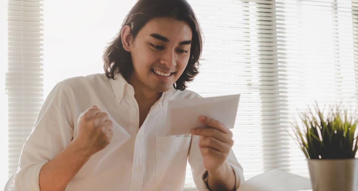 A young man celebrates while holding a job offer letter in his hand. Rewire PBS Work Job Offer