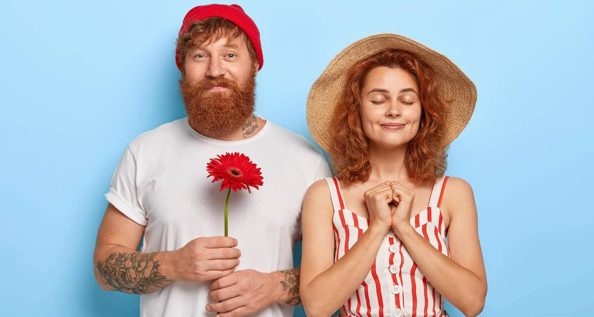 A red-headed couple facing toward the camera. The man has a beard and is holding a flower. The woman has her eyes closed. Rewire PBS Love Past love