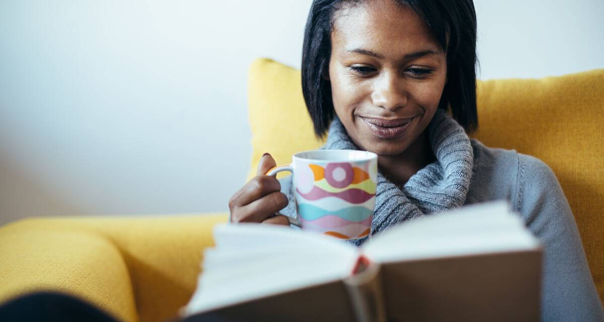 Woman drinking tea and reading a book. Rewire PBS Living alone time