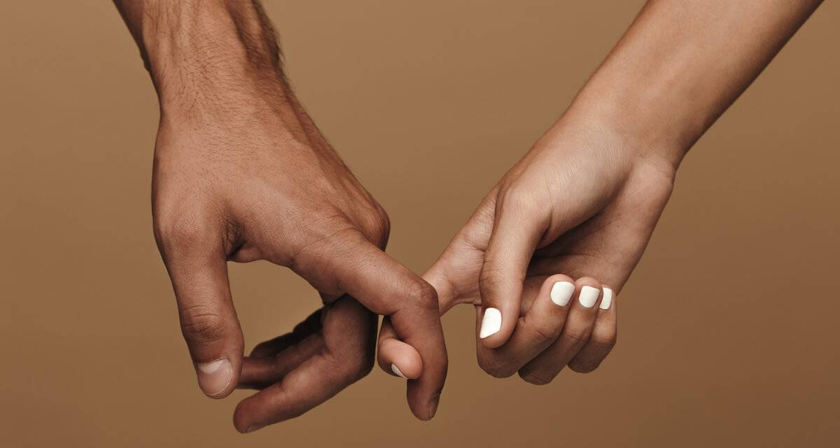 Two people link index fingers over a brown background. Rewire PBS Love Arranged marriage