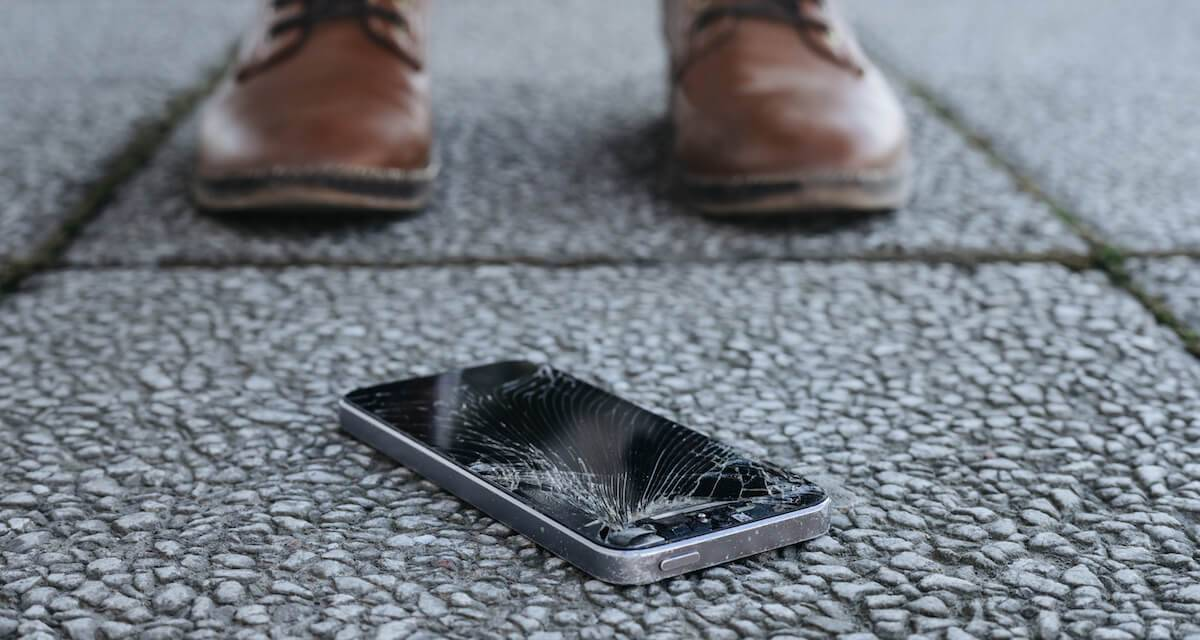 A photo of a broken cellphone on the ground. Rewire PBS Work Vacation