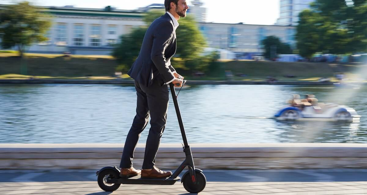 Photo of a young professional male riding an electric scooter. Rewire PBS Our Future Electric Scooters