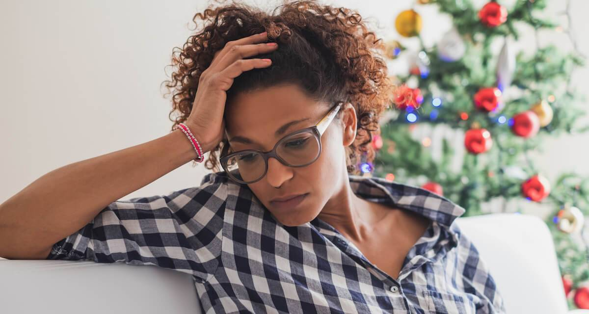 A person sits sadly on a couch with a Christmas tree in the background. Rewire PBS Love Traditions