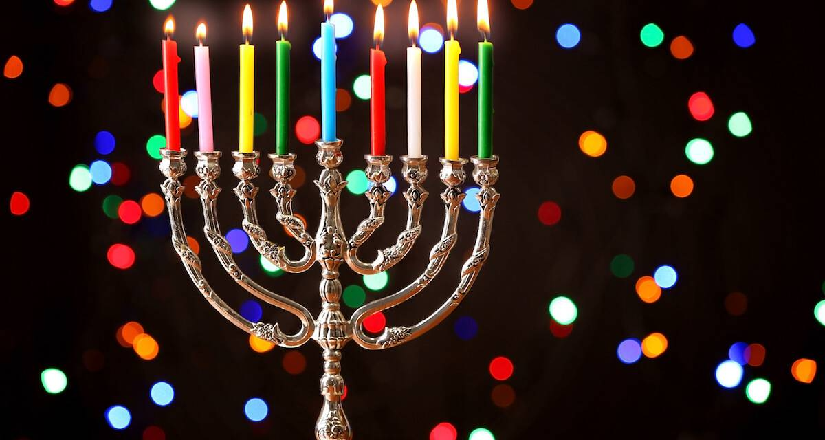 A menorah with colorful candles and colorful defocused lights behind. Rewire PBS Living Hanukkah Movies