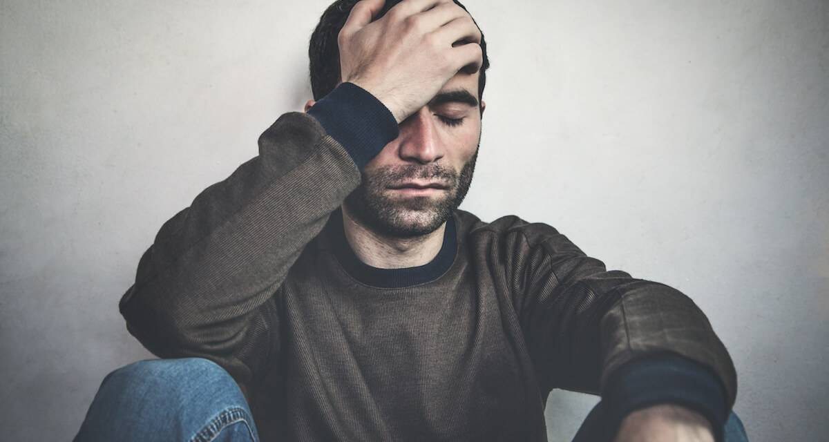 A photo of a person sitting against the wall with his head in his hand. Rewire PBS Love Ambiguous Loss