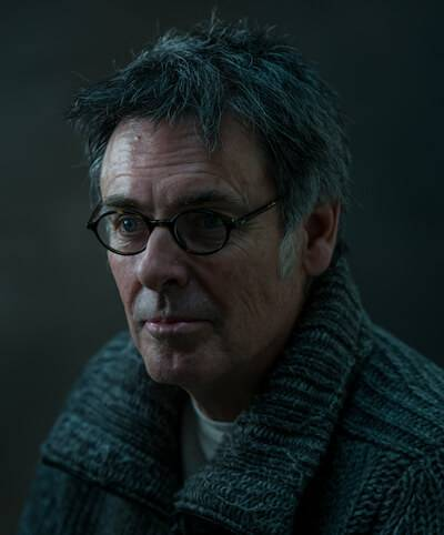 A photograph of filmmaker Michael Kirk, wearing a gray sweater and glasses. Rewire PBS Our Future America's Great Divide