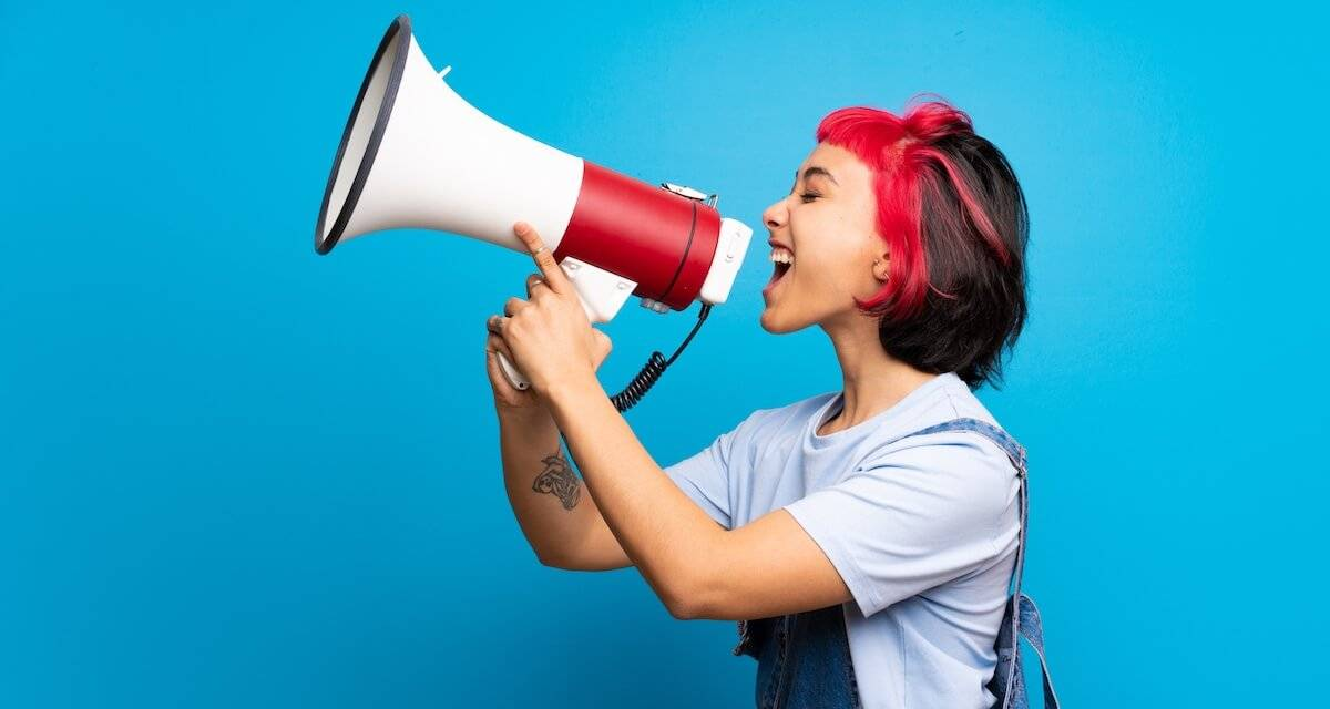 Photo of a woman holding a megaphone in front of a blue background. Rewire PBS Our Future College Student