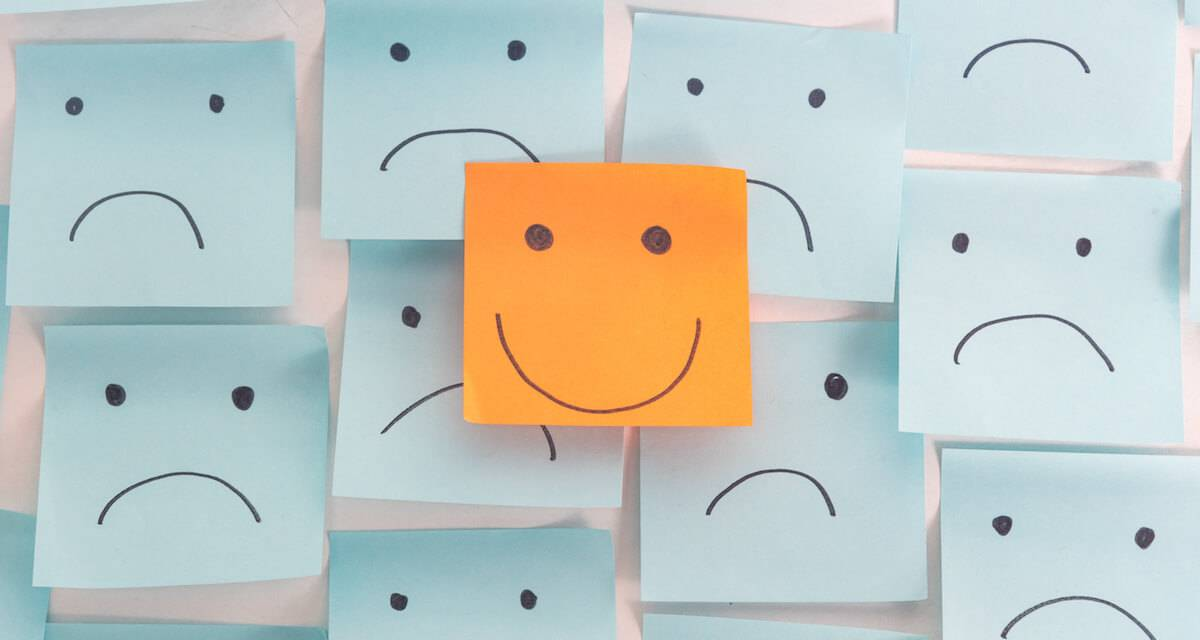 A photo of lots of sticky notes with sad faces on them and one with a happy face. Rewire PBS Work Worst job