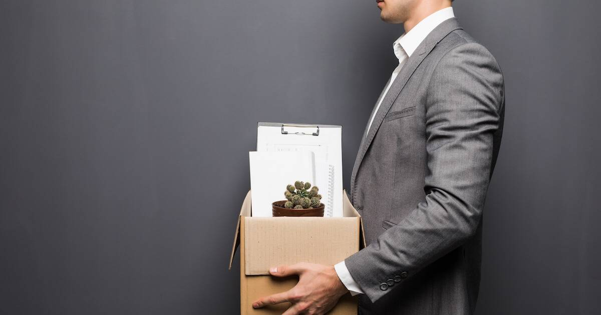 A man in a grey suit holding a box of office stuff. Rewire PBS Work Fired